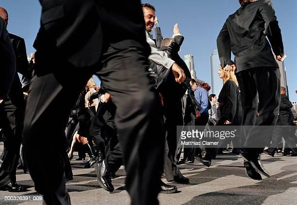 Businesspeople dancing in street, side view