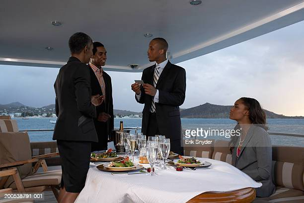 Businesspeople dining on yacht, exchanging business cards