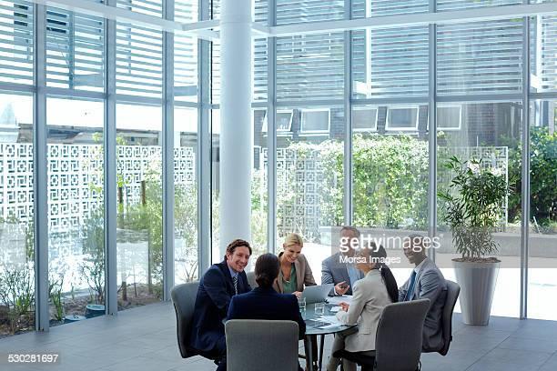 businesspeople discussing at conference table - mondo naturale foto e immagini stock
