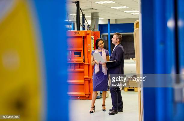 Businesspeople discussing in factory shopfloor