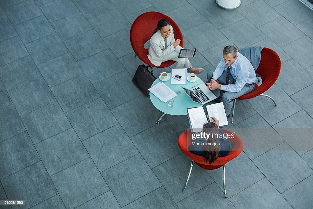 Businesspeople discussing strategy at coffee table : Stock Photo