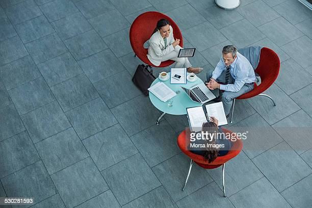 businesspeople discussing strategy at coffee table - three people stock pictures, royalty-free photos & images