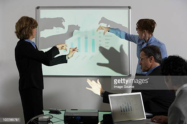 Businesspeople doing shadow puppets in front of whiteboard
