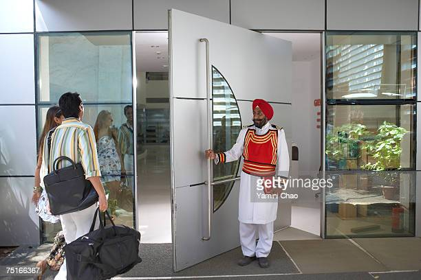 businesspeople entering in office - doorman stock photos and pictures