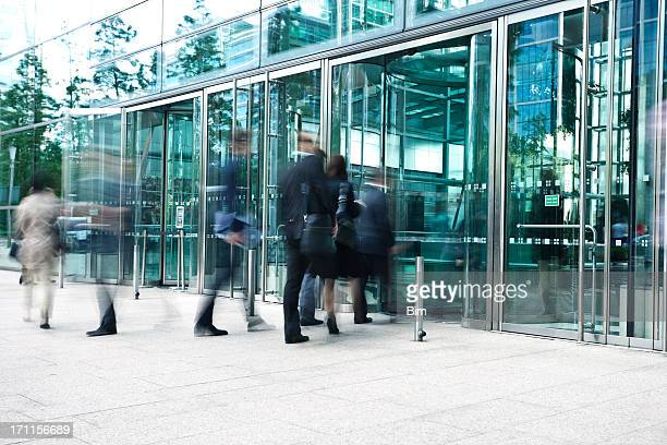 Businesspeople Entering Through Glass Doors of Office Building, Blurred Motion