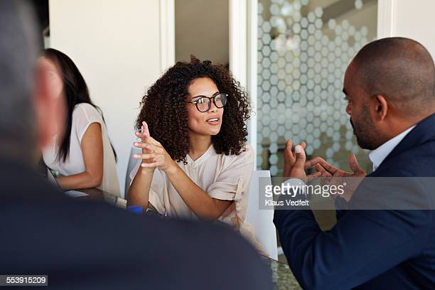 Businesspeople explaining and listening at meeting
