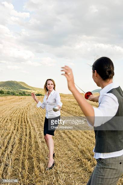 Businesspeople fencing in a wheat field.