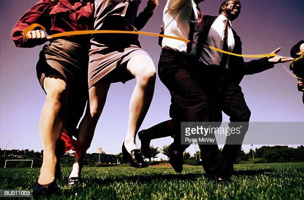 Businesspeople Finishing a Three-legged Race