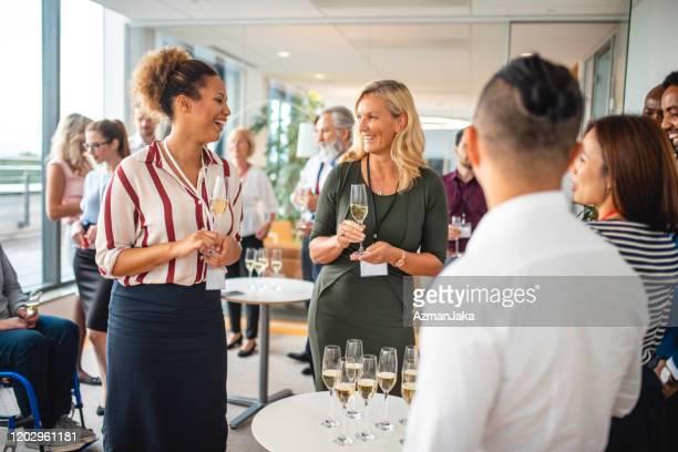 hommes d'affaires rassemblés autour de la table de champagne - soirée de lancement photos et images de collection