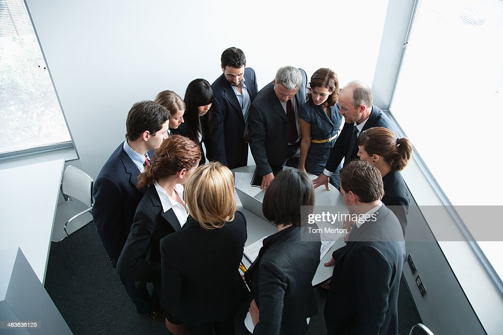 Businesspeople gathering in corner of office : Stock Photo