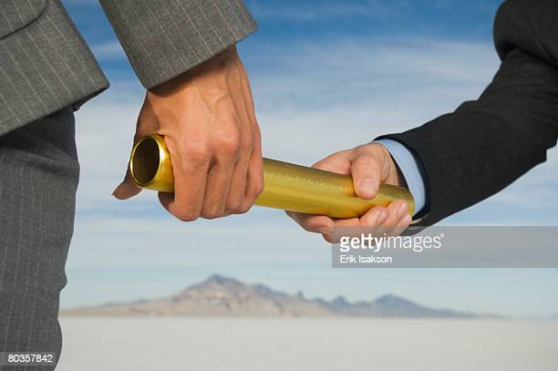 Businesspeople handing off baton in relay race, Salt Flats, Utah, United States