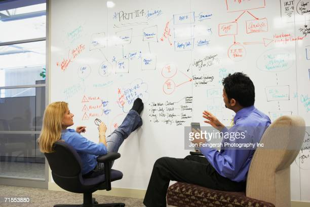 businesspeople having a meeting in front of a whiteboard wall - initiative stock pictures, royalty-free photos & images