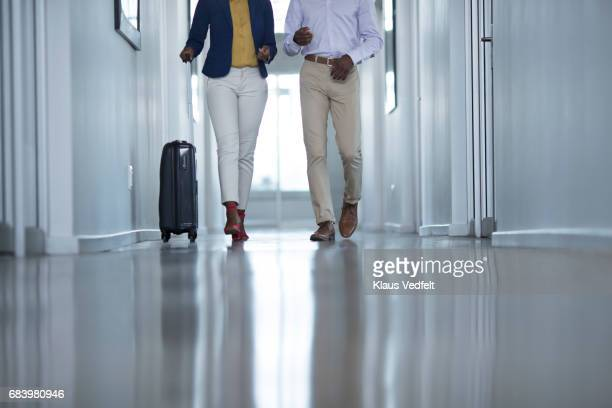 Businesspeople having conversation, while on the way to a meeting