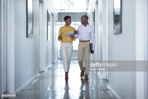 businesspeople having conversation, while on the way to a meeting - black trousers stock pictures, royalty-free photos & images