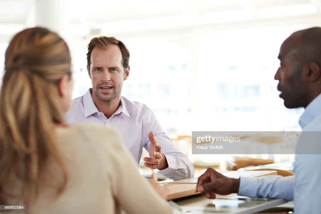 Businesspeople having conversations at restaurant : Stock Photo