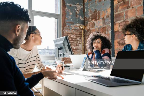businesspeople having discussion with laptops in creative office - nosotroscollection stockfoto's en -beelden
