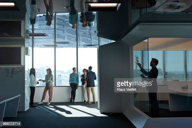 businesspeople having discussions on the isle of large office - labeling stock photos and pictures