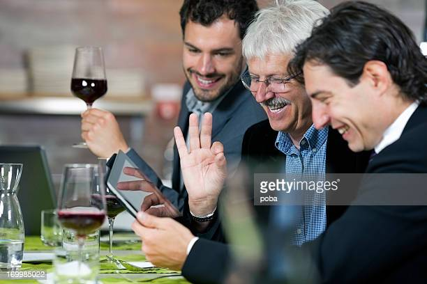 Businesspeople having lunch at restaurant and using digital tablet