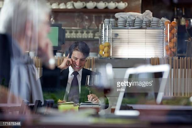 Businesspeople having lunch at restaurant and using mobile  phone