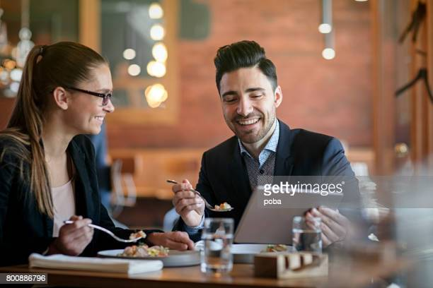 Businesspeople Having Meeting and Lunch In A Restaurant