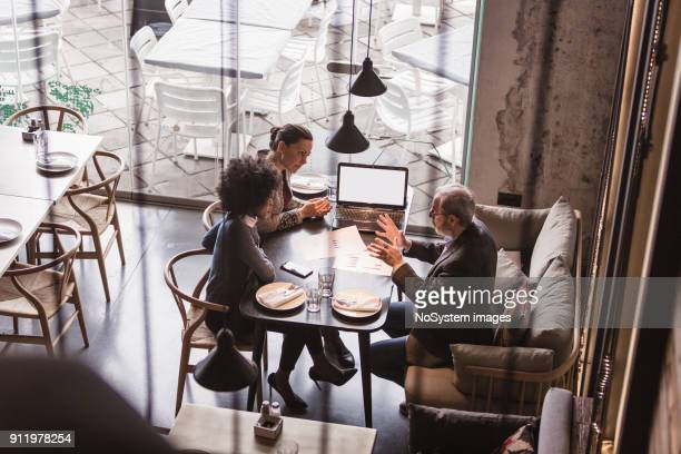 businesspeople having meeting in a restaurant. - bonding stock pictures, royalty-free photos & images