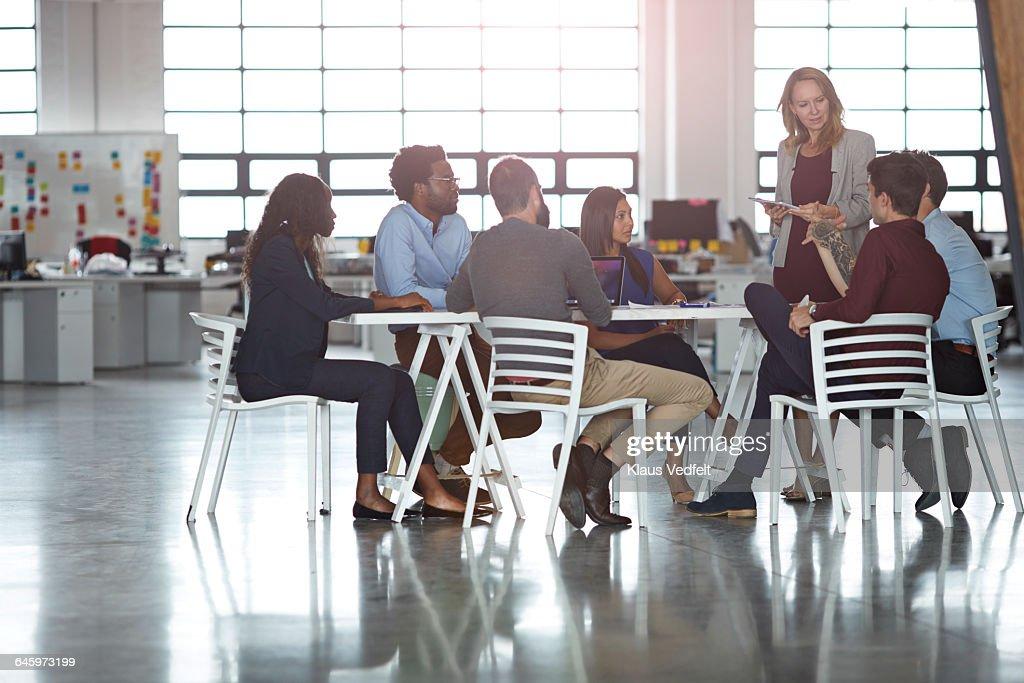 Businesspeople having meeting in big open office : Stock Photo