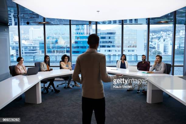 businesspeople having meeting in large futuristic board room - premium access stock pictures, royalty-free photos & images