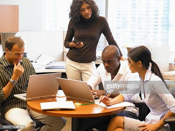 businesspeople having  meeting in office, using laptop computers - flexplekken stockfoto's en -beelden
