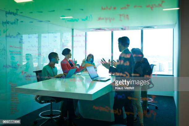 businesspeople having standing meeting at creative agency - blazer vert photos et images de collection