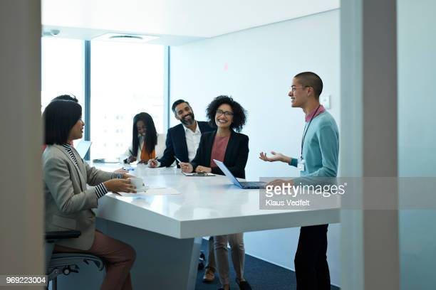 businesspeople having standing meeting at creative agency - non binary gender stock pictures, royalty-free photos & images