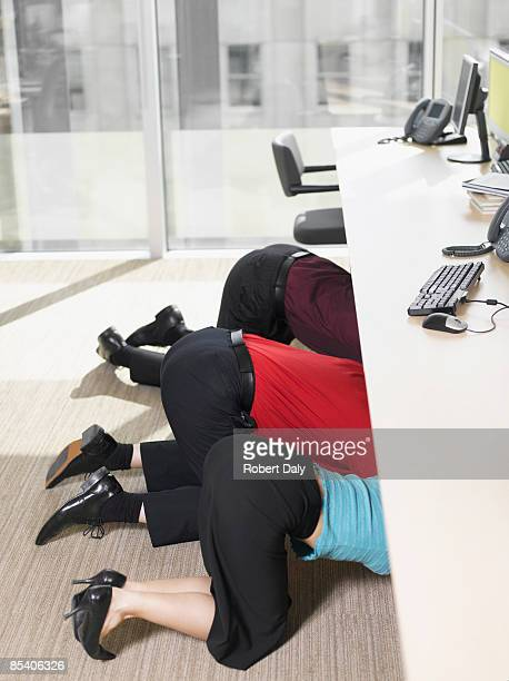 businesspeople hiding under desk in office - vulnerability stock pictures, royalty-free photos & images