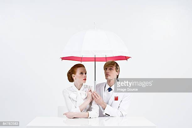 businesspeople holding an umbrella - bad luck stock pictures, royalty-free photos & images