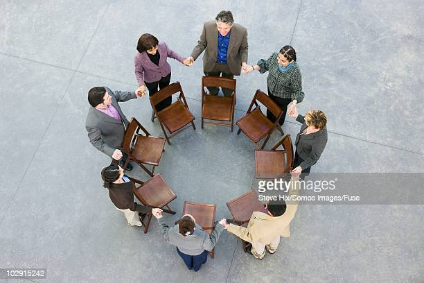 Businesspeople holding hands in a circle