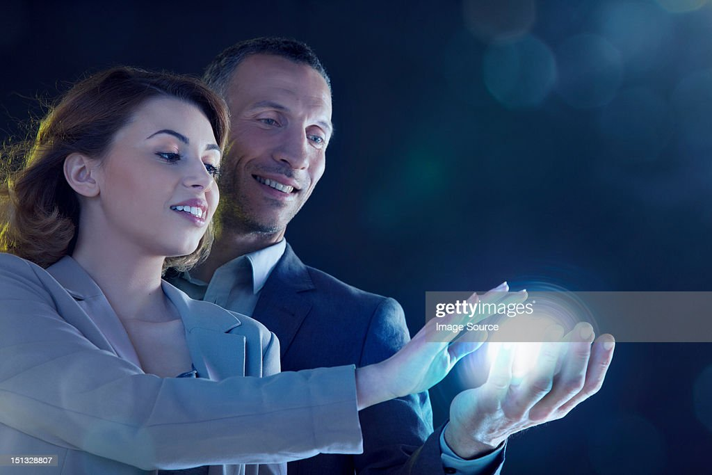 Businesspeople holding light : Stock Photo