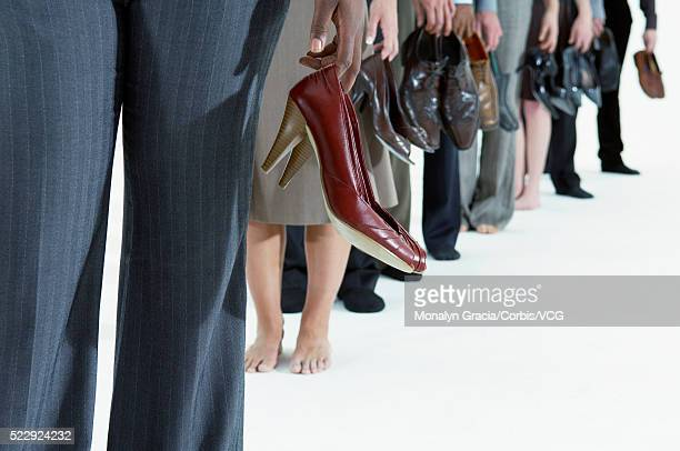 businesspeople holding their shoes - barefoot stock pictures, royalty-free photos & images