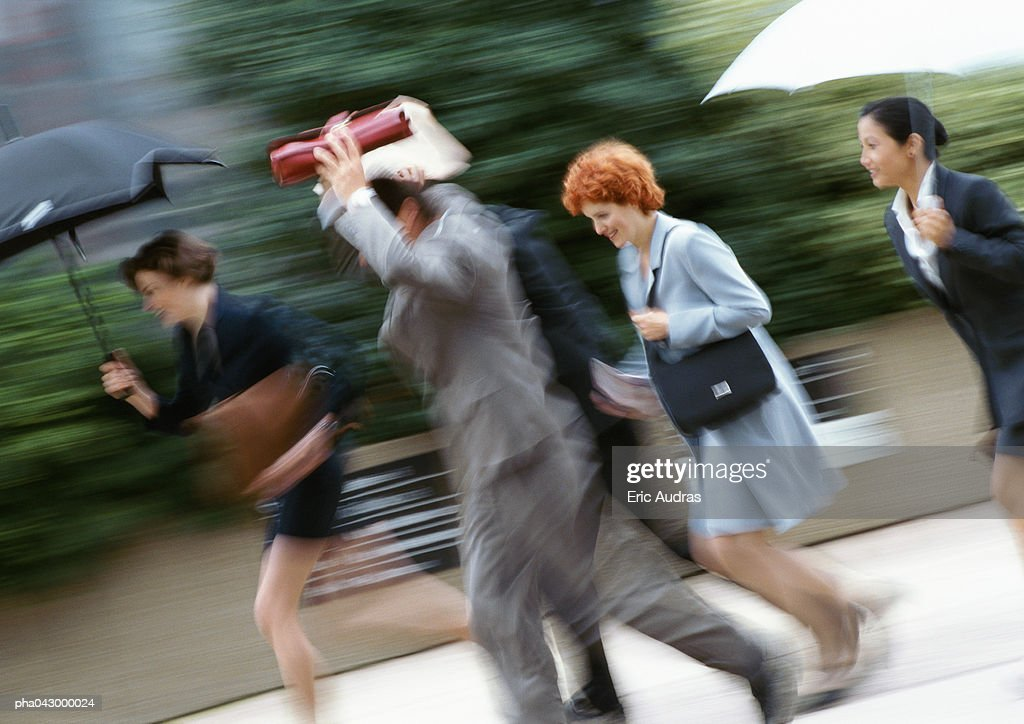 Businesspeople holding umbrella or briefcase above head, running, blurred : Stockfoto