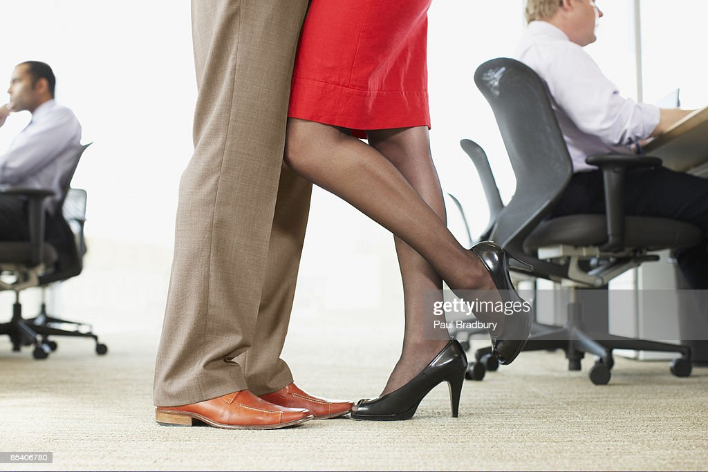 Businesspeople hugging in office : Stock Photo
