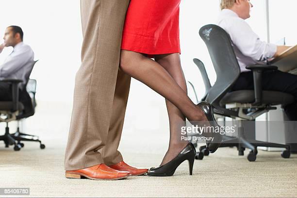 businesspeople hugging in office - kantoorromance stockfoto's en -beelden