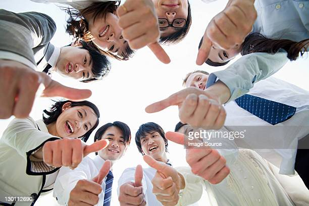 businesspeople in a circle with thumbs up - 作戦会議 ストックフォトと画像