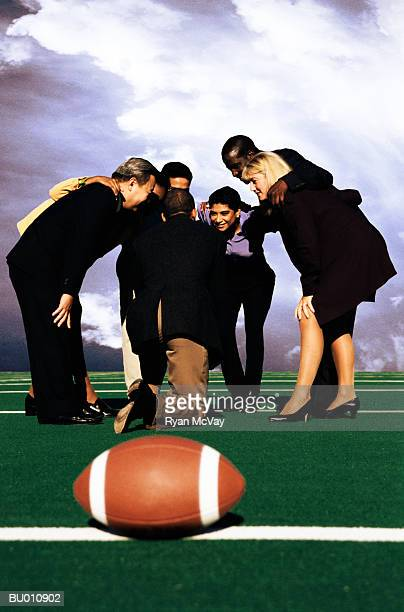 Businesspeople in a Huddle on a Football Field