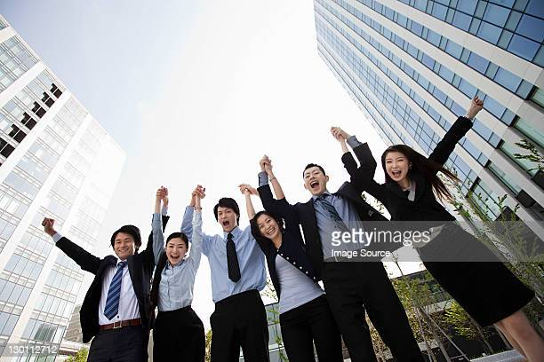 Businesspeople in a row, arms in air