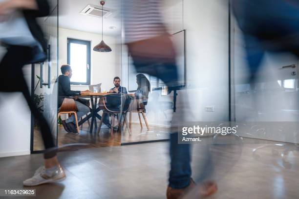 businesspeople in conference room and colleagues walking by - business meeting stock pictures, royalty-free photos & images