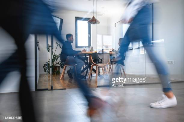 businesspeople in conference room and colleagues walking by - on the move imagens e fotografias de stock
