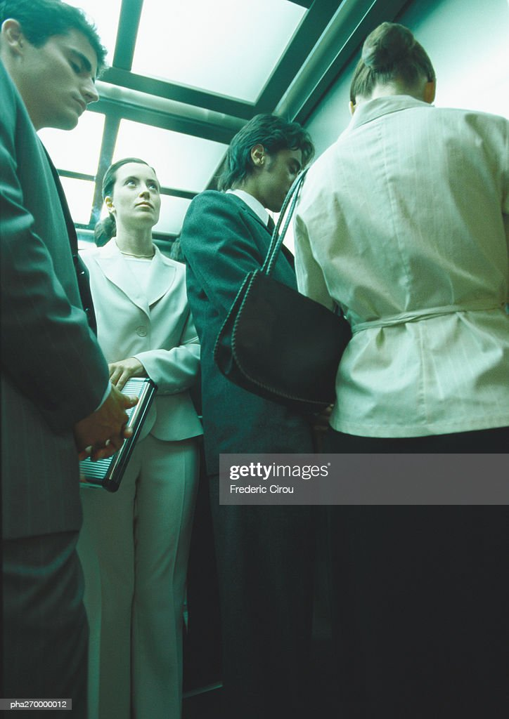 Businesspeople in elevator, low angle view : Stockfoto