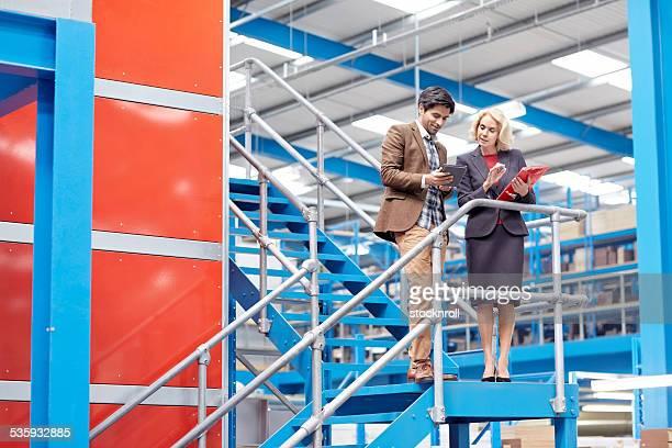 ビジネスマンに工場のデジタルタブレットで作業