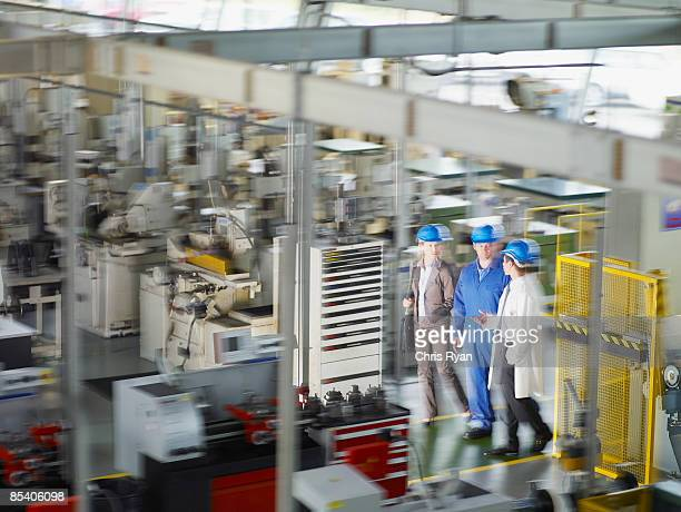 Businesspeople in hard-hats walking on factory floor
