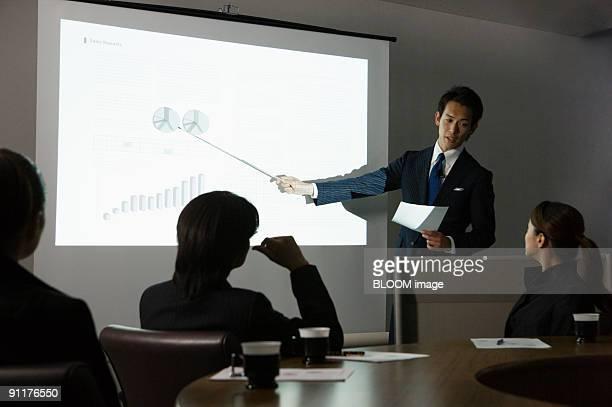 businesspeople in meeting - プレゼン ストックフォトと画像