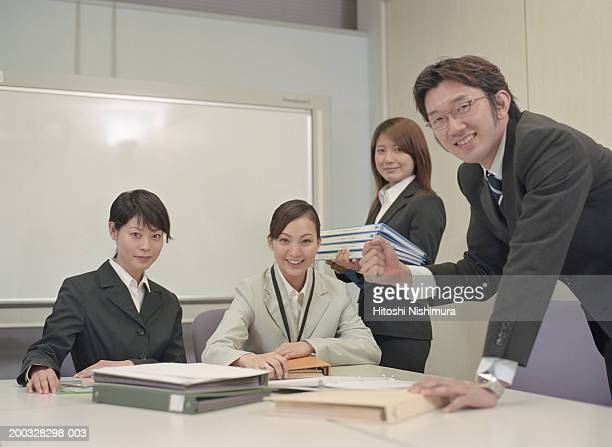 Businesspeople in office, smiling, portrait
