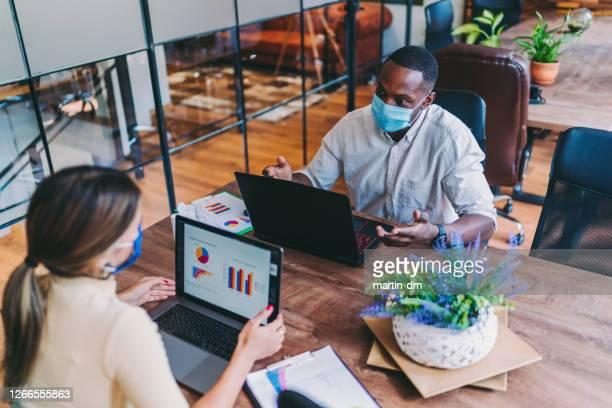 empresários no escritório trabalhando com máscaras faciais protetoras, vírus covid-19 - encarando - fotografias e filmes do acervo