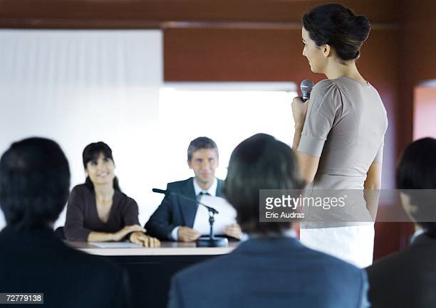 Businesspeople in seminar, one woman standing with microphone